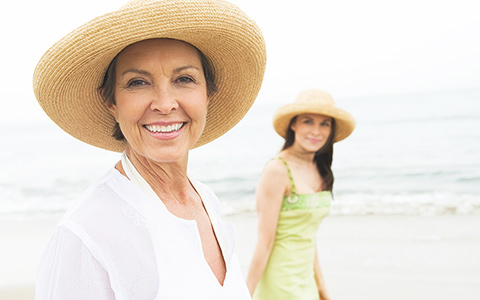 A selfie of a senior woman and her daughter with the ocean in the background.