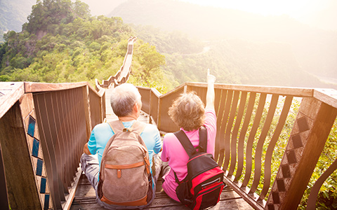 Photo of a senior couple sitting on stairs with a view of beautiful greenery.